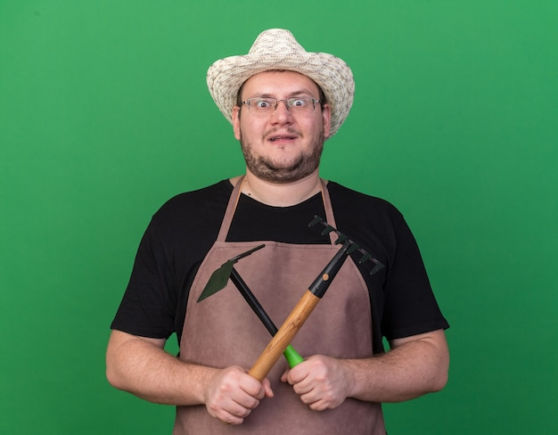 Surpris jeune homme jardinier portant chapeau de jardinage tenant et traversant le râteau avec houe râteau isolé sur mur vert