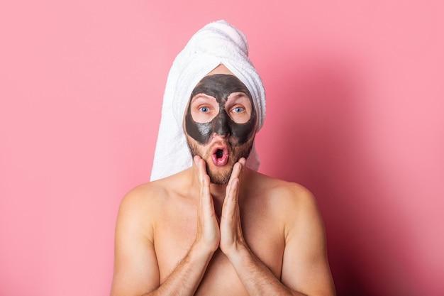 Surpris jeune homme avec un masque cosmétique sur son visage sur fond rose.