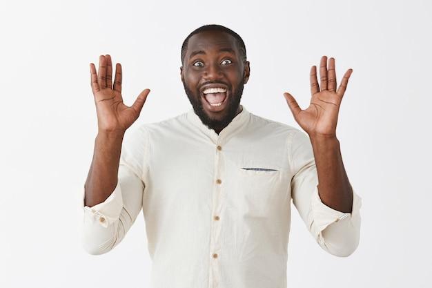 Surpris jeune homme posant contre le mur blanc