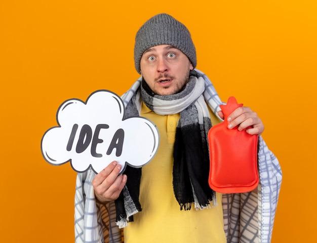 Surpris jeune homme slave malade blonde portant un chapeau d'hiver et une écharpe enveloppée dans un plaid détient une bulle d'idée et une bouteille d'eau chaude isolée sur un mur orange avec espace de copie