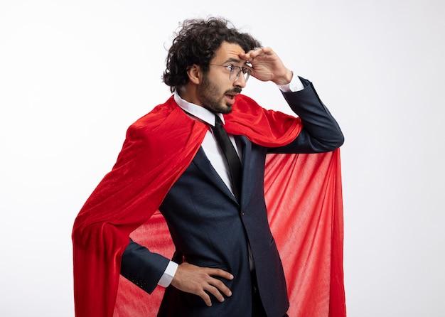 Surpris jeune homme de super-héros dans des lunettes optiques portant costume avec manteau rouge se tient sur le côté en gardant la paume au front à côté isolé sur mur blanc
