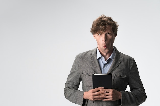 Surpris jeune homme en tenue décontractée tenant un livre dans ses mains isolé sur un mur gris. copiez l'espace à gauche.
