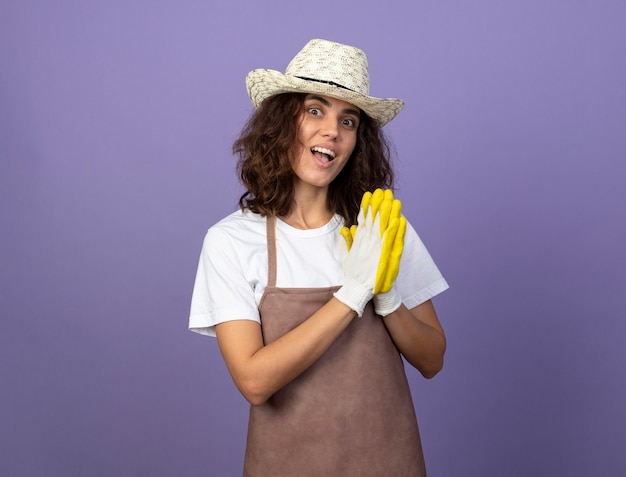 Surpris jeune jardinière en uniforme portant chapeau de jardinage et gants montrant le geste de prier