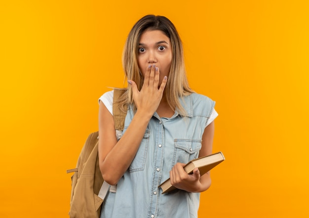 Surpris jeune jolie étudiante portant un sac à dos tenant un livre et mettant la main sur la bouche isolée sur un mur orange