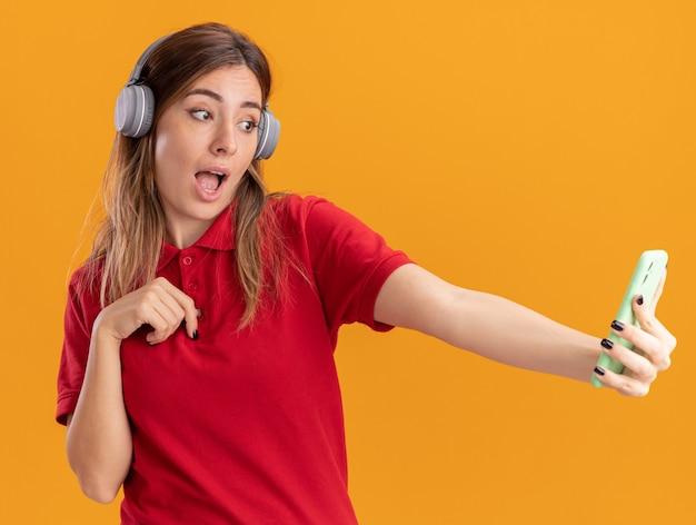 Surpris jeune jolie femme sur le casque tient et regarde le téléphone isolé sur le mur orange