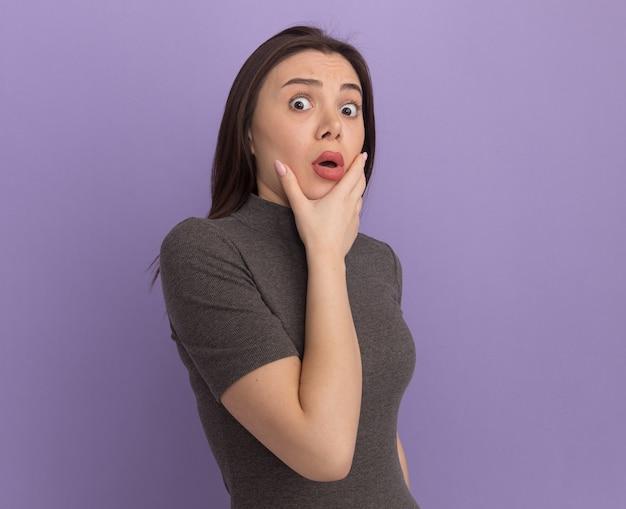 Surpris jeune jolie femme debout dans la vue de profil en gardant la main sur le menton regardant à l'avant isolé sur mur violet avec espace de copie