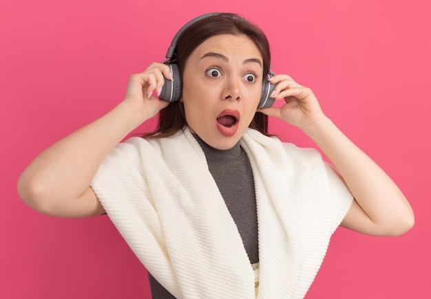 Surpris jeune jolie femme portant et saisissant des écouteurs regardant de côté