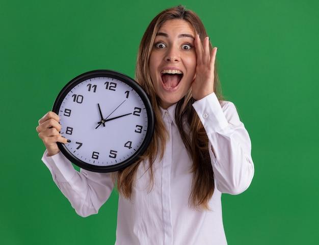 Surpris jeune jolie fille caucasienne met la main sur le visage et tient l'horloge sur le vert