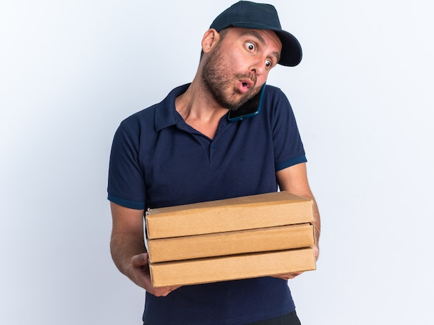 Surpris jeune livreur caucasien en uniforme bleu et casquette tenant des paquets de pizza parlant au téléphone regardant vers le bas isolé sur mur blanc