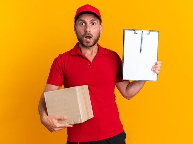 Surpris jeune livreur caucasien en uniforme rouge et casquette tenant une boîte en carton montrant le presse-papiers