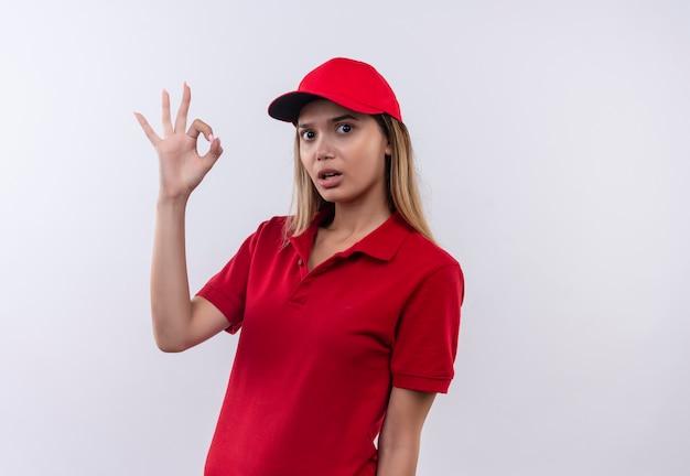 Surpris, jeune, livreur, porter, uniforme rouge, et, chapeau, projection, okey, geste, isolé, blanc, mur