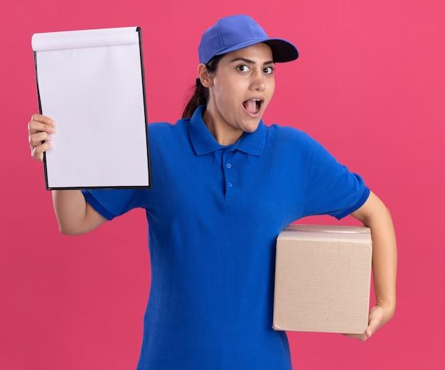 Surpris jeune livreuse en uniforme avec capuchon tenant la boîte avec presse-papiers isolé sur mur rose