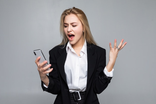 Surpris jolie femme d'affaires bavardant par téléphone debout isolé.