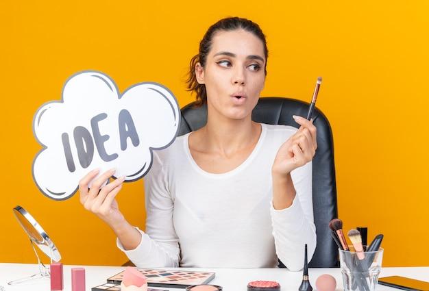 Surpris jolie femme caucasienne assise à table avec des outils de maquillage tenant une bulle d'idée et regardant un pinceau de maquillage