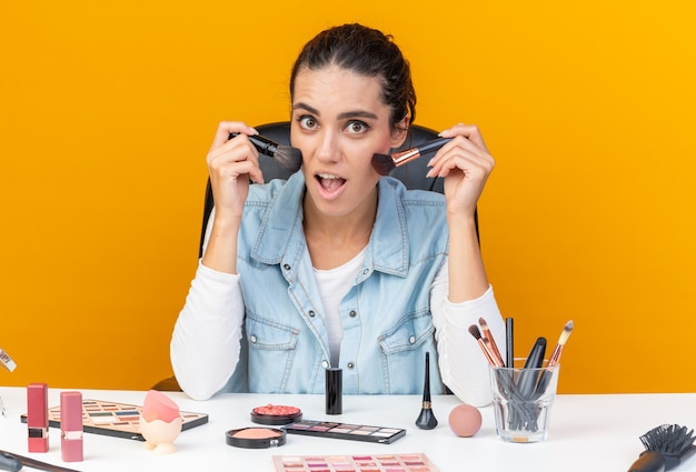 Surpris jolie femme caucasienne assise à table avec des outils de maquillage tenant des pinceaux de maquillage