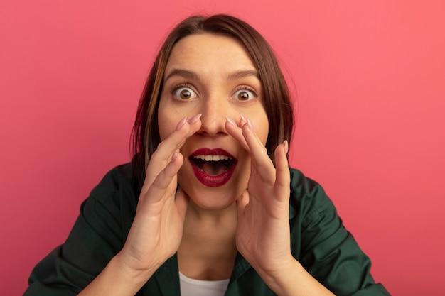 Surpris jolie femme caucasienne tient les mains près de la bouche en regardant la caméra sur rose
