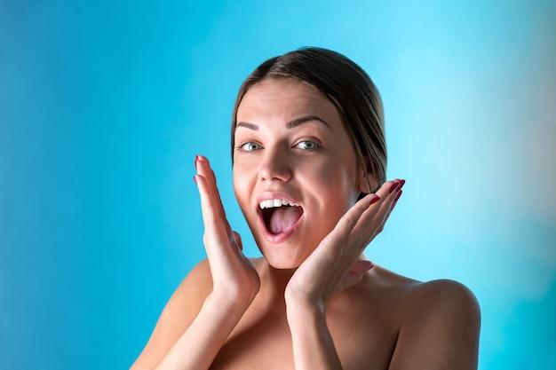 Surpris joyeuse belle femme avec une expression étonnée, regarde avec des yeux buggés et garde la bouche ouverte, sur une surface bleue