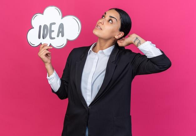 Surpris en levant la belle jeune femme portant un blazer noir tenant une bulle d'idée mettant la main derrière la tête