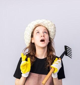 Surpris en levant le jeune jardinier portant un chapeau de jardinage avec des gants tenant un râteau isolé sur un mur blanc