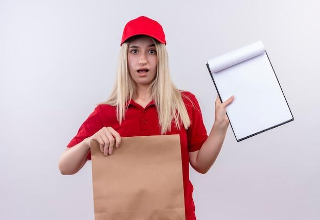Surpris livraison jeune fille portant un t-shirt rouge et une casquette en orthèse dentaire tenant une poche de papier et montrant le presse-papiers sur sa main sur fond blanc isolé