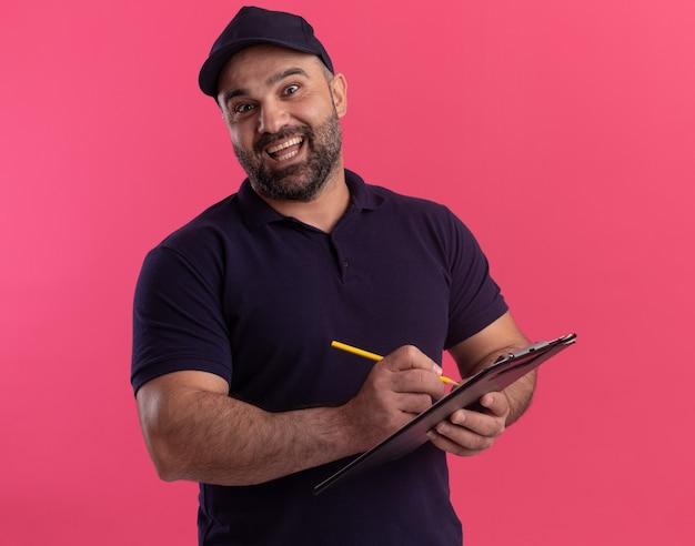 Surpris livreur d'âge moyen en uniforme et cap écrit quelque chose sur le presse-papiers isolé sur mur rose