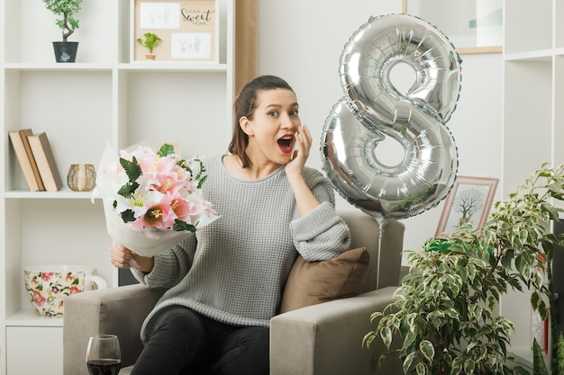 Surpris de mettre la main sur la joue belle fille le jour de la femme heureuse tenant un bouquet assis sur un fauteuil dans le salon