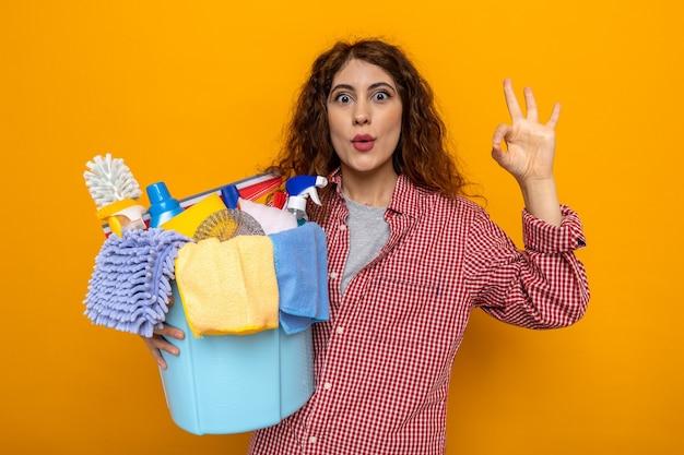 Surpris montrant un geste correct jeune femme de ménage tenant un seau d'outils de nettoyage