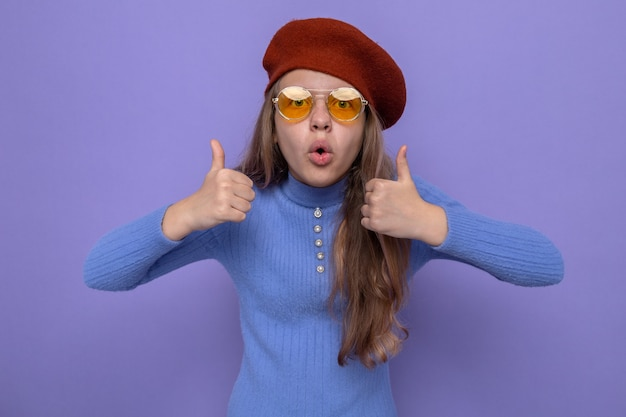 Surpris montrant les pouces vers le haut belle petite fille portant un chapeau avec des lunettes