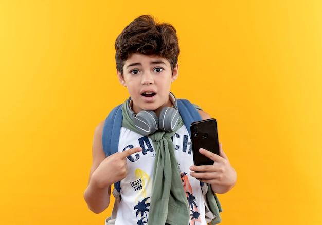 Surpris petit écolier portant sac à dos et écouteurs tenant et points au téléphone isolé sur jaune