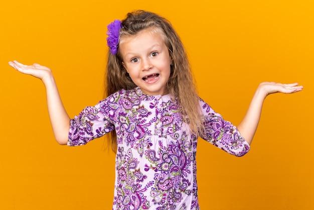 Surpris petite fille blonde en gardant les mains ouvertes isolé sur un mur orange avec espace copie