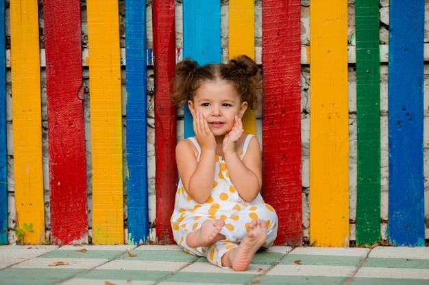 Surpris petite fille est assise à une clôture multicolore