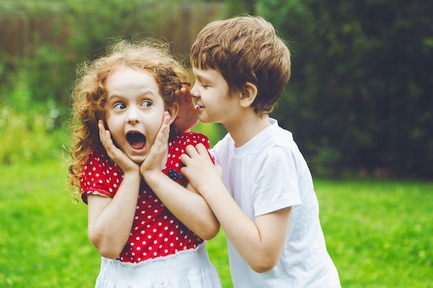 Surpris petite fille et garçon parlant avec des chuchotements.