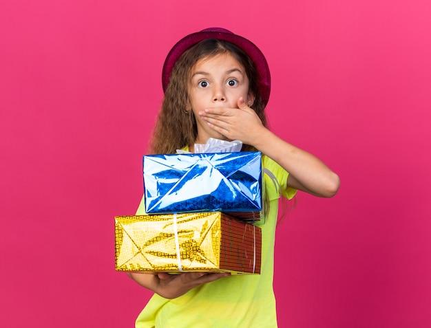 Surpris petite fille de race blanche avec chapeau de fête pourpre mettant la main sur la bouche et tenant des coffrets cadeaux isolés sur un mur rose avec espace copie