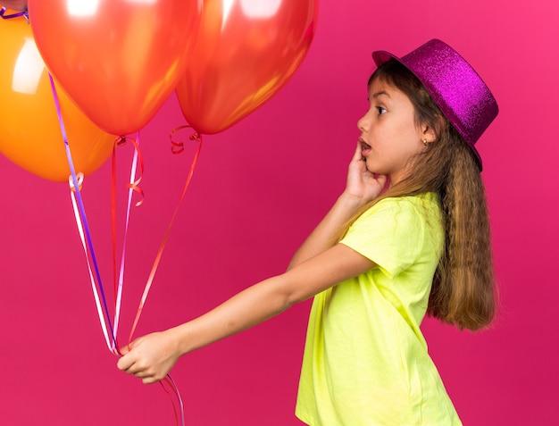 Surpris petite fille de race blanche avec chapeau de fête pourpre mettant la main sur le visage tenant et regardant des ballons d'hélium isolés sur un mur rose avec espace de copie