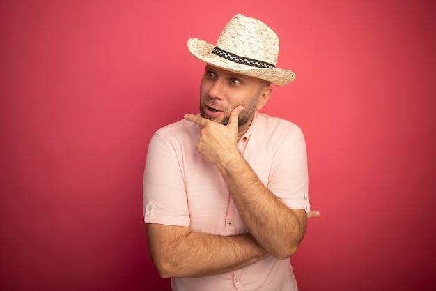 Surpris à la recherche à côté homme chauve d'âge moyen portant un t-shirt rose et un chapeau mettant la main sur le menton isolé sur rose