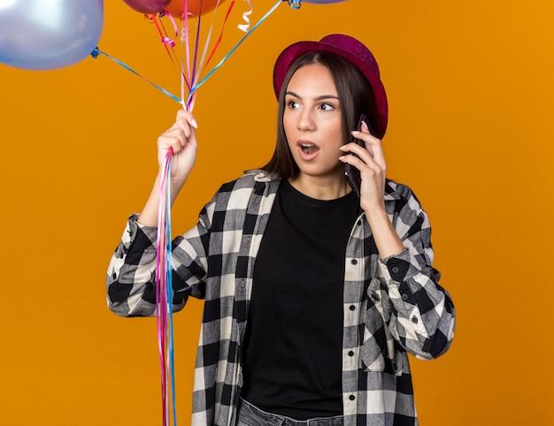 Surpris en regardant côté belle jeune fille portant un chapeau de fête tenant des ballons parle au téléphone