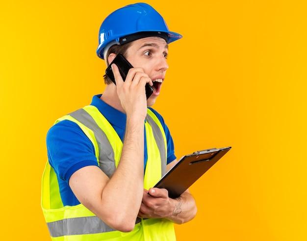 Surpris en regardant un jeune constructeur en uniforme tenant un presse-papiers parle au téléphone isolé sur un mur jaune avec espace pour copie