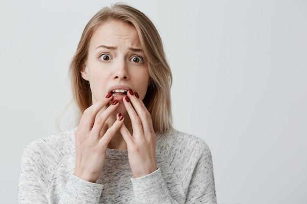 Surpris surpris jeune blonde séduisante avec des cheveux teints femme wearingsweater ayant l'expression du visage étonné, couvrant sa bouche ouverte avec les mains