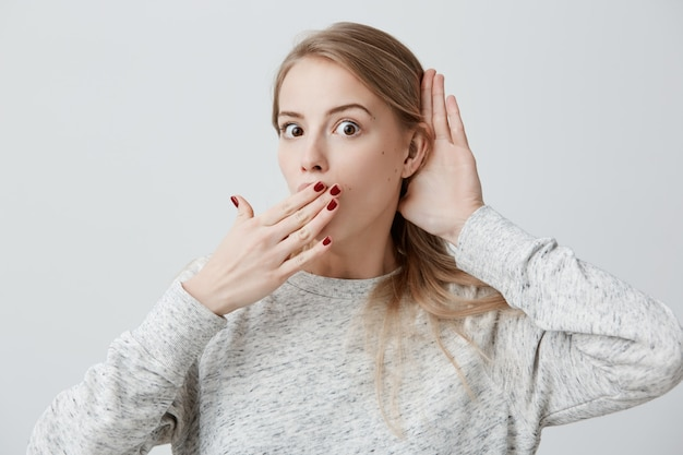 Surpris surpris jeune femme blonde séduisante ayant l'expression du visage étonné, couvrant la bouche ouverte avec la main