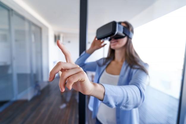 Surpris surpris jeune femme avec des lunettes de réalité virtuelle touchant l'air pendant l'expérience vr à la maison