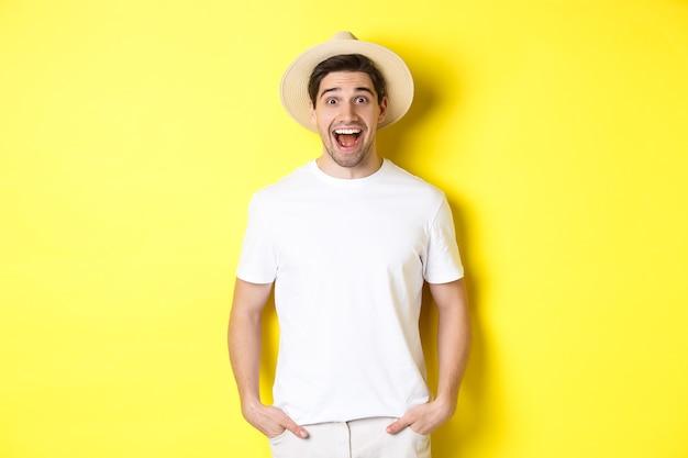Surpris touriste homme au chapeau de paille à la recherche de plaisir, réagir étonné de la publicité de l'agence de voyage, debout sur fond jaune.