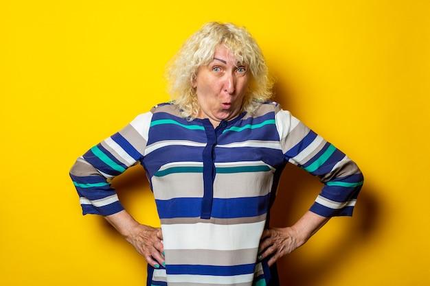 Surpris vieille femme dans une robe rayée tient ses mains à la taille sur une surface jaune