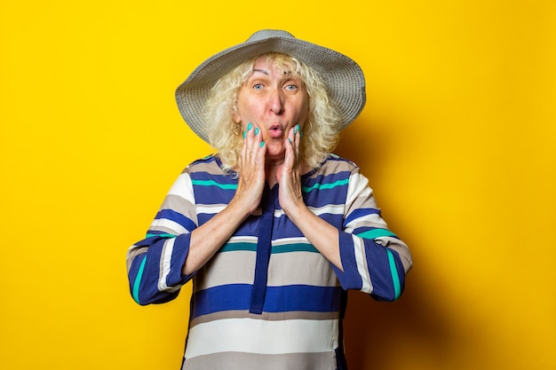 Surpris vieille femme en robe et chapeau tient ses joues avec ses mains sur une surface jaune