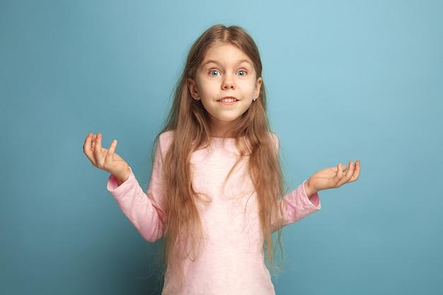 Surprise, délice, bonheur, joie, victoire, succès et chance. fille adolescente surprise sur un fond de studio bleu. concept d'expressions faciales et d'émotions de personnes.