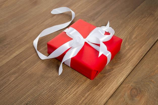 Surprise en emballage rouge sur fond de bois