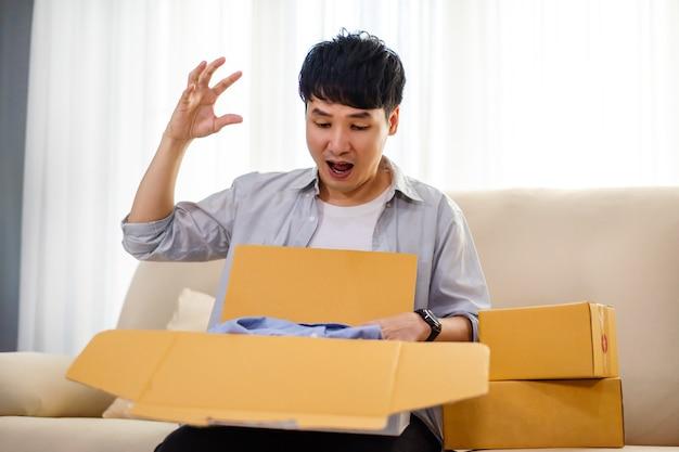 Surprise homme boîte à colis en carton ouverte dans le salon à la maison, achat sur boutique en ligne
