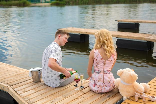 Surprise de rendez-vous romantique. un jeune homme et une fille sur une jetée en bois. le gars verse du champagne dans les verres.