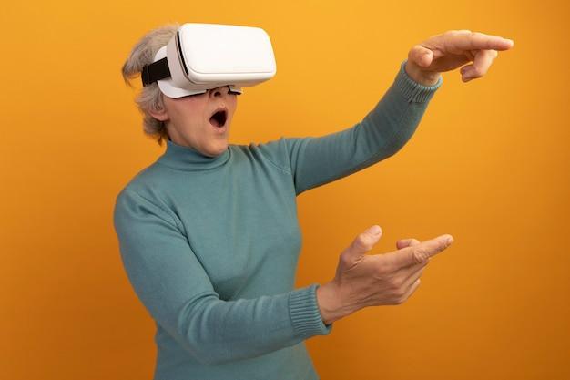 Surprise vieille femme portant un pull à col roulé bleu et un casque vr regardant et pointant sur le côté isolé sur un mur orange