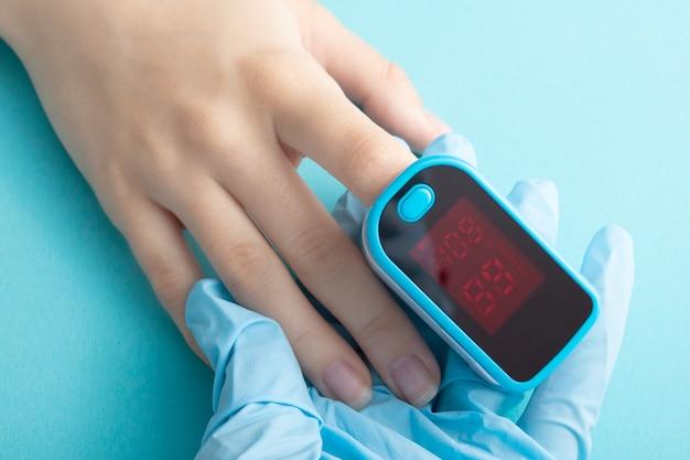Surveillance de la saturation en oxygène du sang avec un appareil spécial sur un doigt féminin sur fond bleu