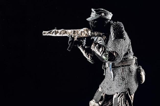 Survivant de l'après-apocalypse nucléaire, soldat nazi d'histoire alternative ou partisan en casquette de champ de laine, masque facial, lunettes et armure faite à la main, visant une mitraillette en studio photo, fond noir